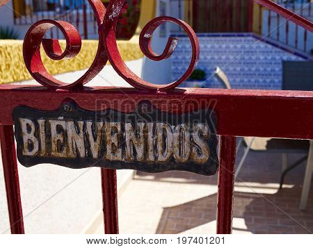 Welcome sign in Spanish Bienvenidos on a gate of a house Spain