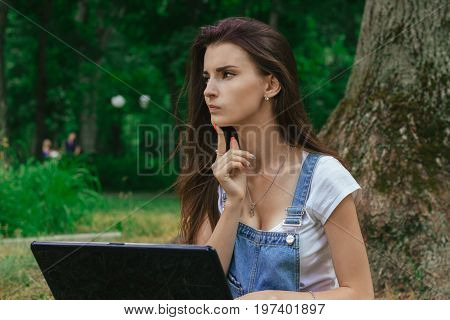 beautiful thoughtful Lady with the laptop in the Park close-up