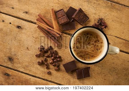 Mug with hot coffee and arabica coffee beans with broken dark chocolate cocoa powder cinnamon sticks and anise on wooden rustic table.