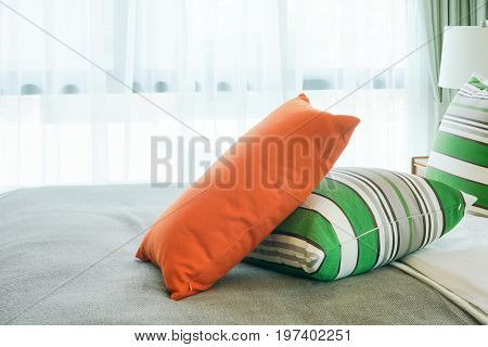 Orange Pillow On Green Stripped Pillows On Bed Next To Window
