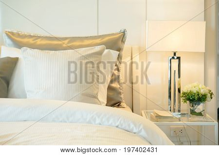Closeup Pillows On Bed With Modern Reading Lamp At Home