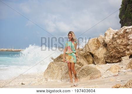 Horizontal portrait of beautiful blonde girl in colorful dress is standing on the beach in front of stones and looking down