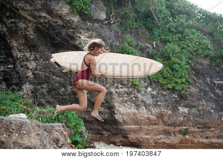 Excited surf girl in dark-red swimming suit with a surfboard is jumping from a cliff