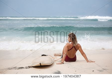 Attractive surf girl in dark-red swimming suit is sitting on the beach next to a surfboard in front of the ocean and looking away