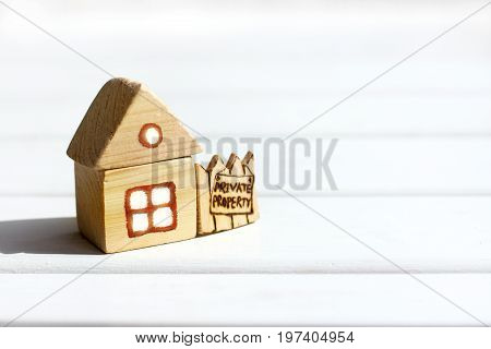 Breadboard model of a small wooden house with a fence and a signboard / private property