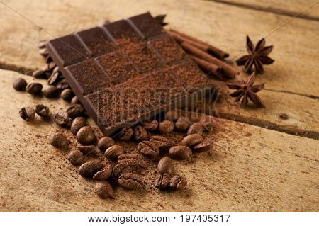 A large bar of dark chocolate arabica coffee beans cinnamon and anise on old wooden rustic background with copy space.