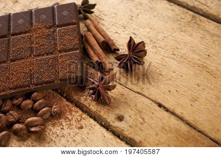 Close-up of roasted arabica coffee beans dark chocolate bar and spices anise with cinnamon stick and cocoa powder on old rustic wooden background with copy space.