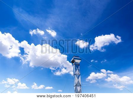 Shiny steel smokestack and cloud in blue sky
