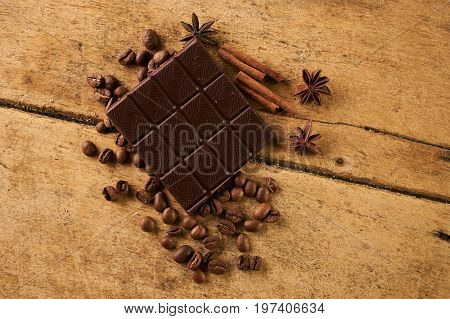 Coffee beans and cinnamon on a old rustic wooden background. Roasted arabica coffee beans pile with cinnamon stick and anise spice ingredients for fragrant coffee.