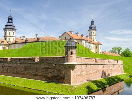Ancient castle with a moat. Old castle towers and walls reflecting in the pure river water picturesque background