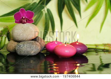 Pebbles arranged in zen lifestyle on the left with an orchid at the top and three lit pink candle