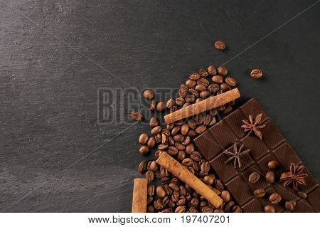 Aromatic set of chocolate bar arabica coffee beans anise and cinnamon on dark stone background with copy space