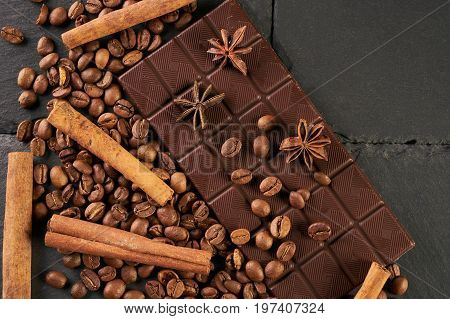 Close-up of roasted arabica coffee beans dark chocolate bar and spices anise with cinnamon on dark stone background with copy space.