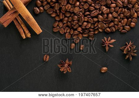 Aroma coffee ingredients. arabica coffee beans anise and cinnamon on dark stone background.