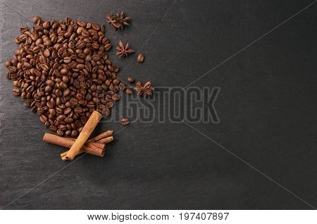 Cinnamon sticks with anise star flavoring and arabica coffee beans on dark stone background with copy space.