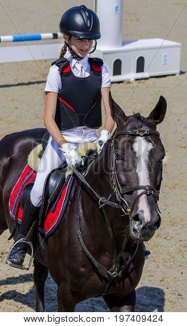Young girl with black horse. Blond pretty little girl going jump a hurdle in a competition. Girl with crow horse during equestrian showjumping. Bright sunny day.