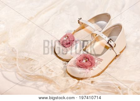 Small baby girl booties on lace dress as background