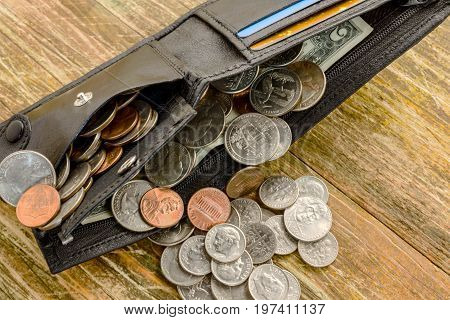 Concept of saving money in a crisis and home finances. Finance and savings. A lot of cents are scattered and in a purse on a wooden table. And banknote two dollars.