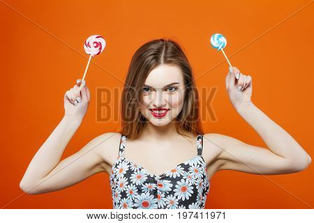 Portrait Of Young Girl In Eyeglasses Holding Two Lollipops In Hands On Orange Background. Cute Brune