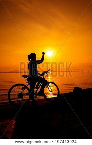 Silhouette of happy woman her arm up towards the sun with mountain-bike on colorful orange sky background. Active outdoors lifestyle for healthy concept. Action of winner or successful people.