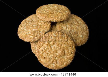 A pile of oatmeal biscuits on a wooden board. The biscuits are piled in the centre of the board and are piled on top of each other. A focus stacked image Isolated on a black background.