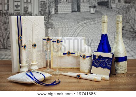 Decorated wedding accessories on a wooden table. A set of wedding accessories decorated in Colored tapes and jewelry