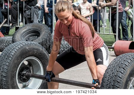 Almaty , Kazakhstan - May 28, 2017. Young girl lifts a heavy barbell. Weightlifting. City fesitwal sport on the street for a healthy lifestyle. Sports contests for arm-wrestling, heavy lifting, tug-of-war