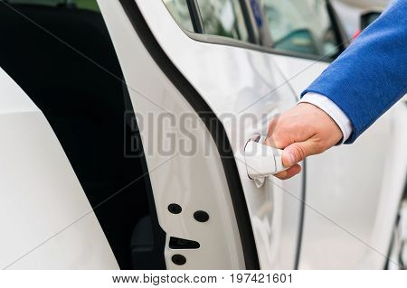 The person's hand holds the handle of the car door and opens the car close-up
