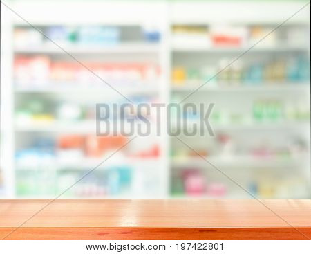 Wooden tabletop for product display with blurred drugstore shelves background.