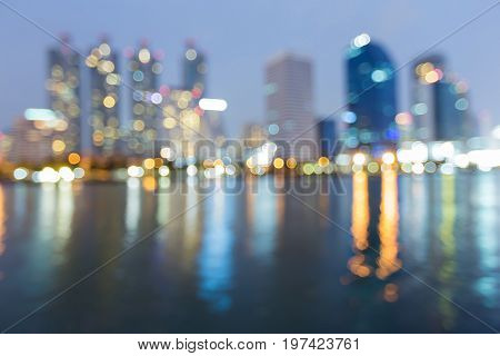 Blurred bokeh light city office building with water reflection at twilight abstract background
