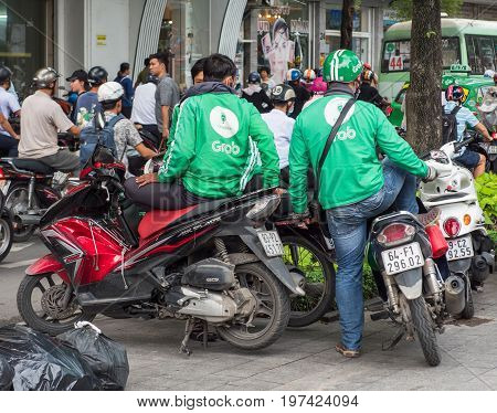 Ho Chi Minh City Vietnam - July 28 2017: Motorbike taxi driver from the controversial Grab ride-sharing system in downtown Ho Chi Minh City. Grab and the similar Uber have been accused of pressing prices and thereby redusing earnings for the drivers.