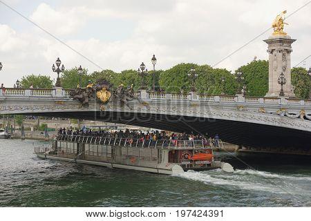 ParisFrance- April 29 2017: Ship with tourists floats under the bridge of Alexander lll