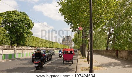 ParisFrance- April 29 2017: On the Tuileries embankment there are cars motorcycles with passengers and a stroller with a tourist