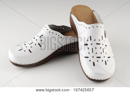 Beautiful modern pair of white clogs isolated on grey background