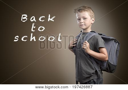 Back to school concept young boy with back bag against blackboard