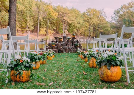 Wedding decoration with autumn pumpkins and flowers. Ceremony outdoor in the park. White chairs for guests. Close-up