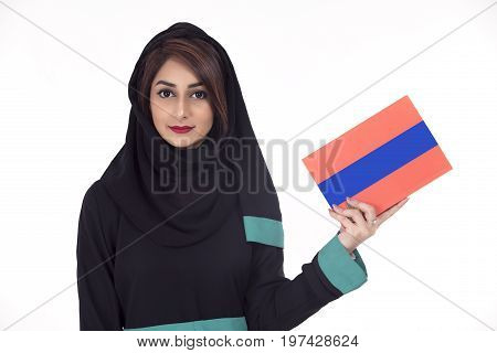 Arabic student wearing hijab and holding a book in her hand