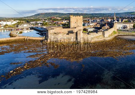 Medieval Norman Castle in Carrickfergus near Belfast in sunrise light. Aerial view with marina yachts parking and town in the background.