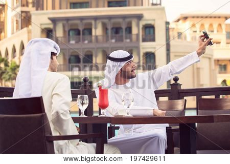 two Arab man taking a selfie in a cafe and drink red juice at Dubai in evening