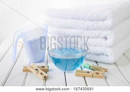 Stack of three white fluffy bath towels washing powder in measuring cup blue fabric softener in a glass bowl and wooden clothespins on the background of white boards