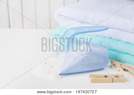 Stack of white and blue fluffy bath towels washing powder spilled from a measuring cup and wooden clothespins on the background of white boards