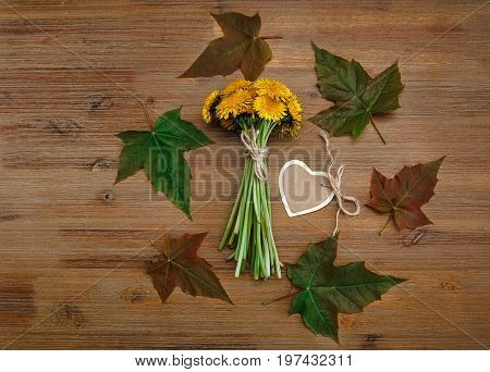Posy of Yellow Dandelions.Heart Wish Card,Green Leaves.Autumn Garden's Background.Wooden Table.Top View