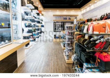 Blurry Background of inside Camera Store with camera bag and camera accessories.