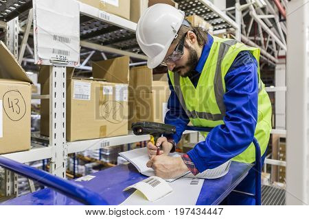 Male labor wearing blue uniform yellow jacket and hard hat writing leaning on table holding barcode reader.