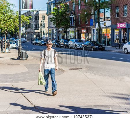 Montreal, Canada - May 27, 2017: Young Man Crossing Street On Saint Laurent Boulevard In Montreal's