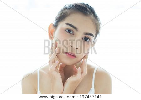 A beautiful woman asian using a skin care product moisturizer or lotion taking care of her dry complexion. Moisturizing cream in female hands .