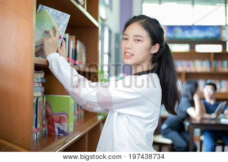 Asian female students holding for selection Book in library