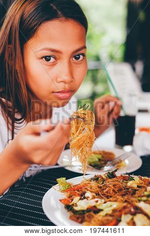 Young asian woman at the restaurant eating stir fry rice noodle with meat and vegetables Philippine food call pansit bihon