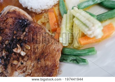 Roast pork with with garlic on top and vegetable side dish. Pork Plate with Vegetables