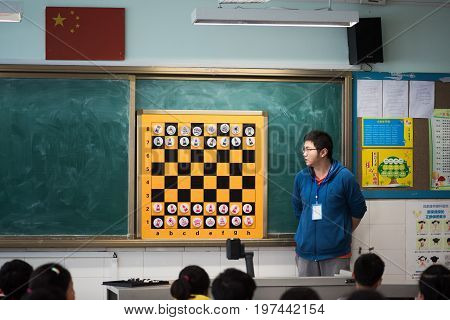 Chengdu, Sichuan Province, China - March 31, 2017: Teacher giving a chess lesson to children in a chinese classroom